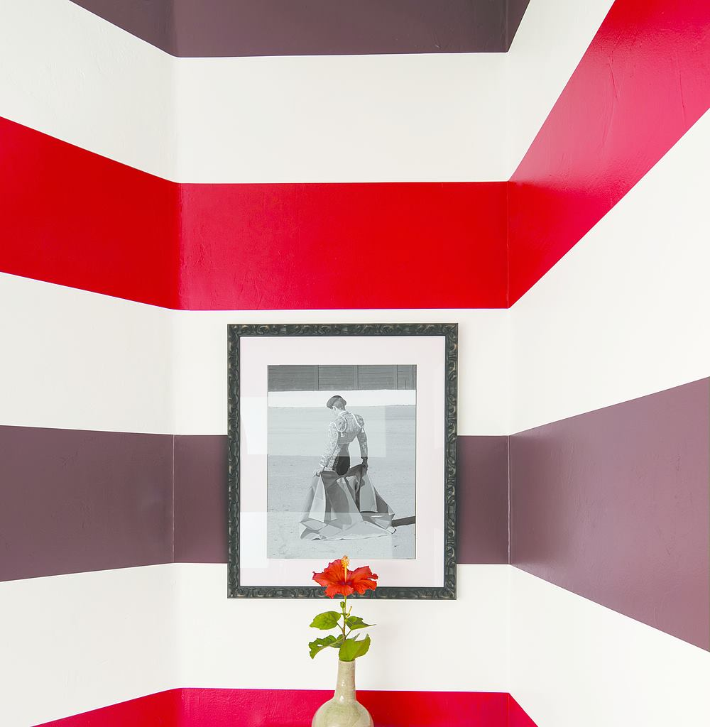 Wall showing black and white photo, vase and stripes on the wall in Garrison Red HC-66, Atrium White OC-145 and Bonfire 2001-20