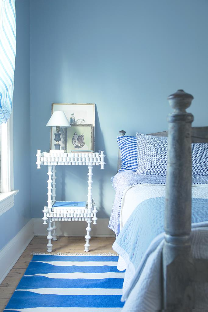 Room showing blue walls, bed and white side table. Popular Interior Paint Colors