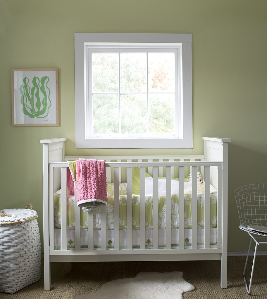 white baby crib against a window with white frame