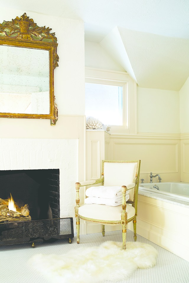 bathroom tub with chair and fireplace