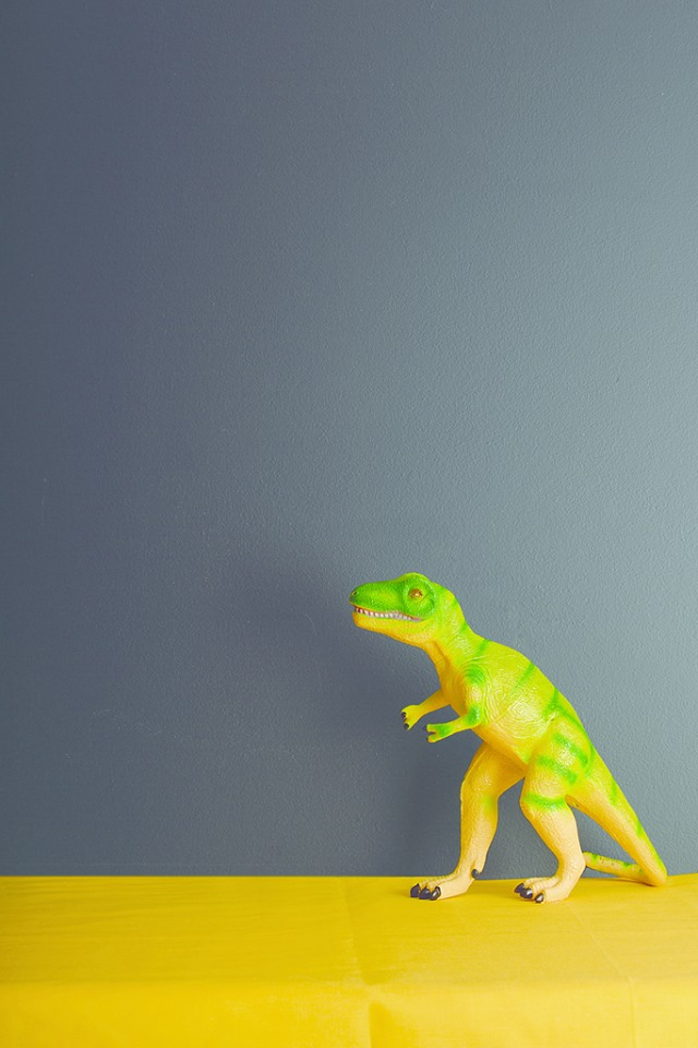 gray wall with green dinosaur on a yellow table