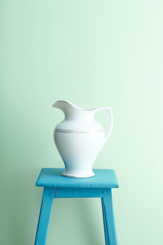 White vase on a turquoise table and light green walls Duanesburg