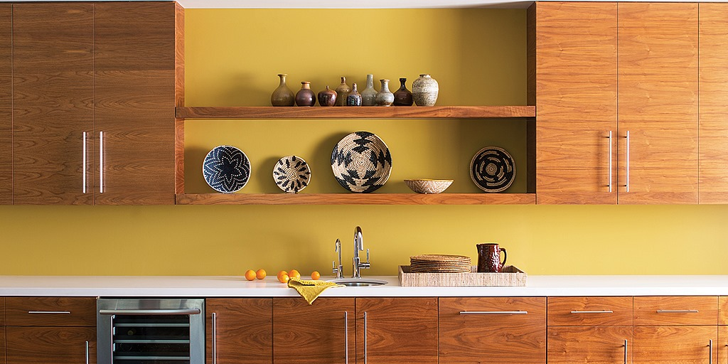 Wooden shelves with yellow call and kitchen cabinets below
