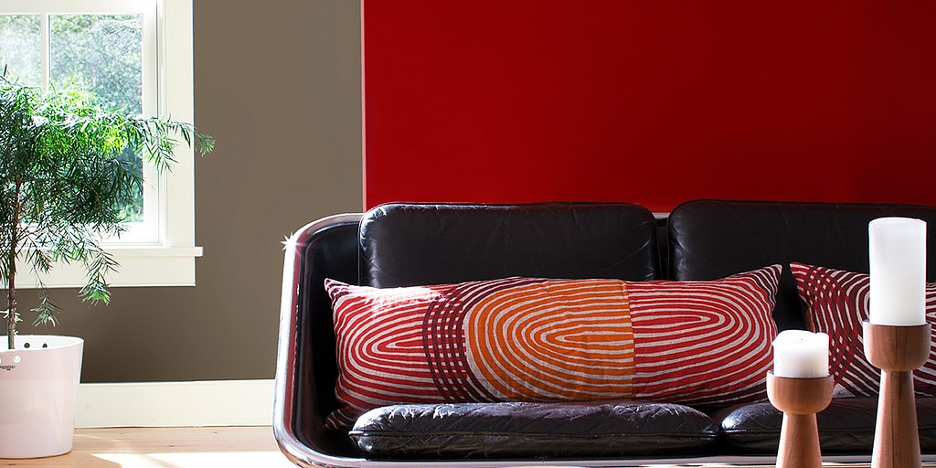 Dark red wall with modern couch and pillows