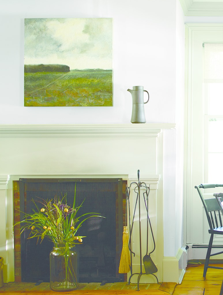 Fireplace with flowers in front and painting above it