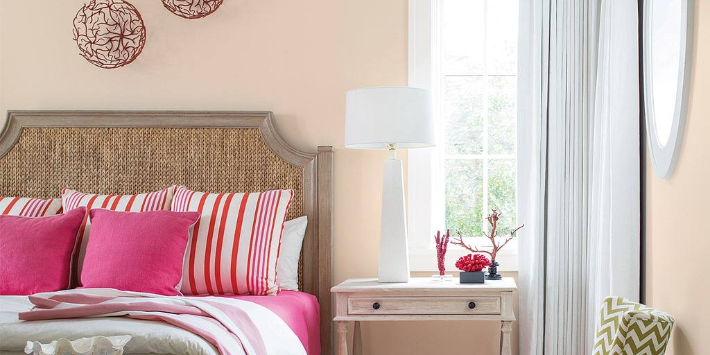 Bedroom with pink blanket and pillows and window with side table and lamp