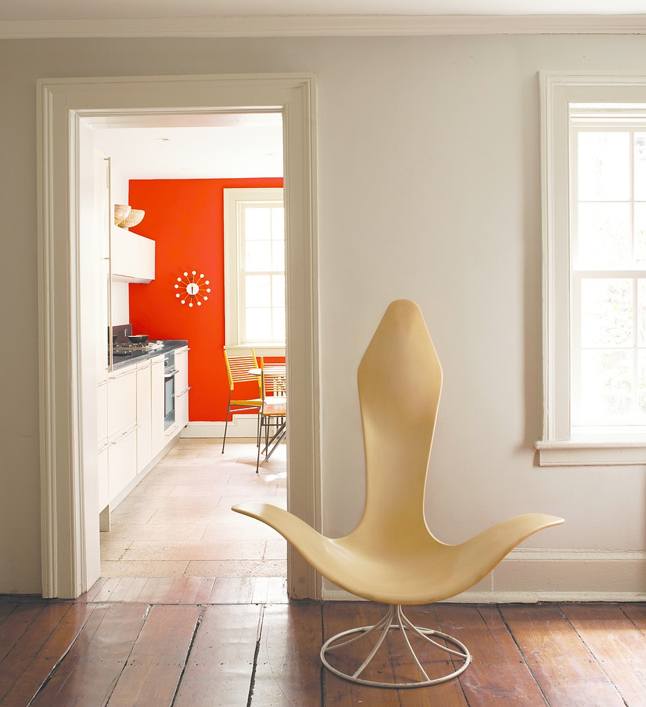 Modern chair in front of hallway with red wall in background